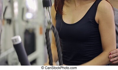 Woman trains her arms with rope in gym under guidance of trainer.