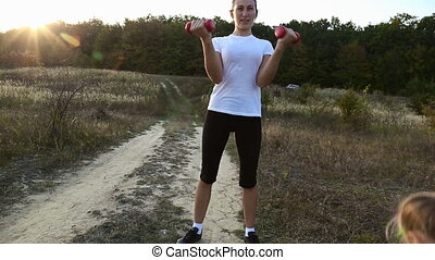Woman trains with dumbbells