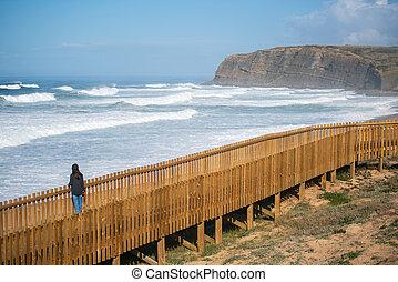 Woman traveler at Praia Azul beach in Torres Vedras, Portugal