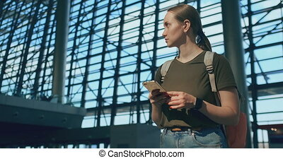Woman traveler at the airport looking at the...