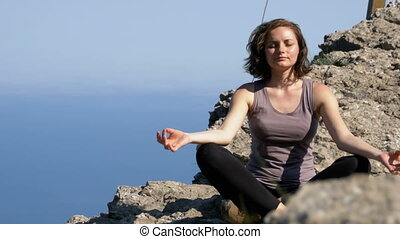 Woman traveler meditates in mountains, sitting on top of a...