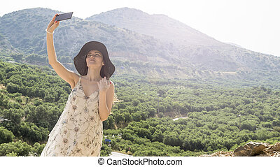 Woman traveler photographing beautiful natural view mountains on the island of Crete. Concept - tourism, travel, photos from vacation