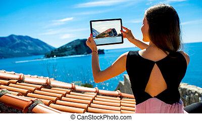 Woman traveler photographing St. Nikola island in Budva