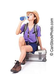 Woman traveler sitting on suitcase