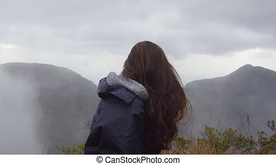 Woman traveler sitting on the edge of beautiful canyon and looking at nature. Young female tourist in raincoat enjoying view in the mountains. Close up Side view