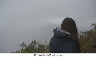 Woman traveler sitting on the edge of beautiful canyon and looking at nature. Young female tourist in raincoat enjoying view in the mountains. Slow motion Close up Rear back view
