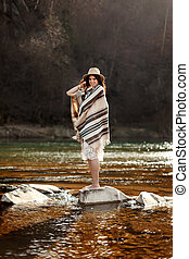 woman traveler standing on rocks in river, wearing hat and poncho, boho travel concept