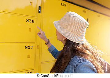 Woman traveler using the locker service and go vacation in the city.  Travel concept