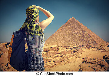 woman traveler with a backpack and the pyramids at Giza,...
