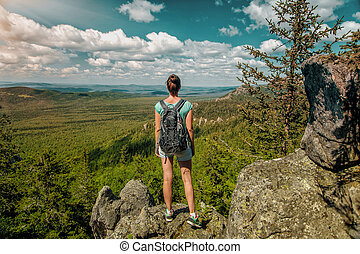 Woman Traveler with Backpack hiking in Mountains with beautiful landscape
