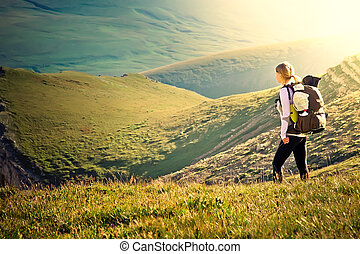 Woman Traveler with Backpack hiking in Mountains with...