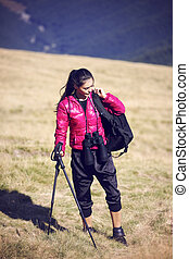 Woman Traveler with Backpack hiking in Mountains with beautiful summer landscape on background mountaineering sport lifestyle concept