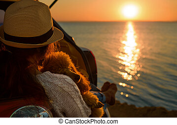 Woman traveler with dog sitting in car trunk near the sea.