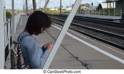 Woman traveler with mobile waiting for train on platform