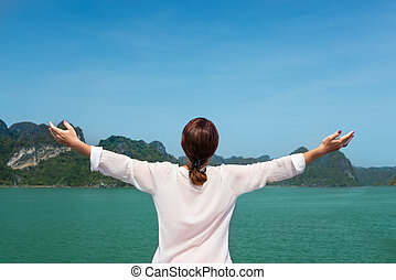woman traveling by boat among the islands with arms up feeling free bliss back view