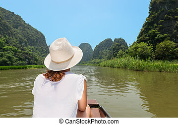 Woman traveling by boat on river among the islands