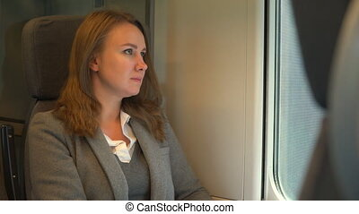 Woman traveling by train and looking thru the window.