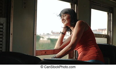 woman traveling by train looking out the open window