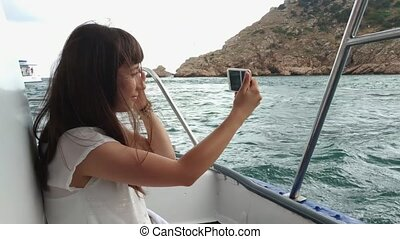 Woman traveling by yacht and take a pictures