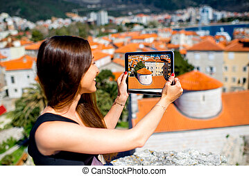 Woman traveling in Budva city - Young woman photographing...