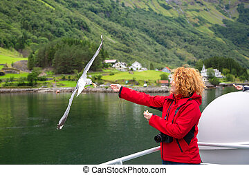 Woman traveling on ferry boat and feeding seagull