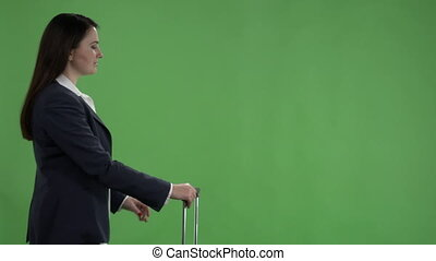 Woman traveling with luggage waving to taxi against a green screen