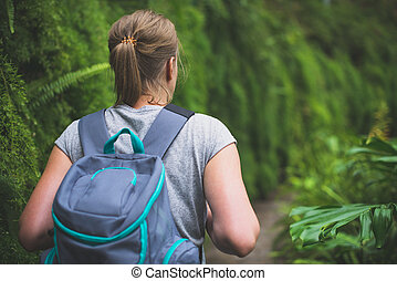 Woman traveller with backpack in the forest.