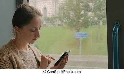 Woman travelling by bus and using smartphone. Travel,...