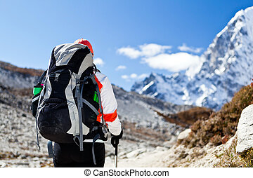 Young woman hiker hiking in Himalaya Mountains in Nepal. Focus on a backpack.