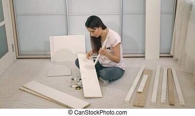 Woman try to assemble furniture - Young woman trying to...