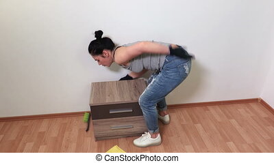 Woman try to moves the nightstand get back pain injury