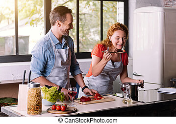 Woman trying a dish cooked with husband - We should try it....
