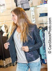 Woman trying a jacket on in a shop