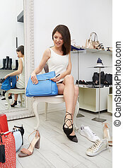 woman trying bags and  shoes sitting in a shop