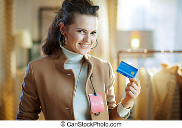 woman trying coat with sale price tag and holding credit card