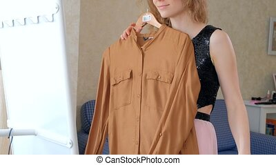 Woman trying new clothes in front of a mirror at home