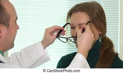 Woman trying new eyeglasses with ophthalmologist against bright window