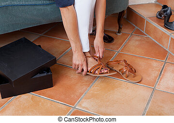 Woman Trying New Sandals In Store - Low section of woman...