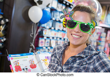 woman trying novelty sunglasses in store