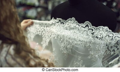 Woman trying on designer white transparent lace on a black mannequin.