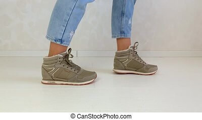 Woman trying on sneakers - Women's slim legs in jeans and ...