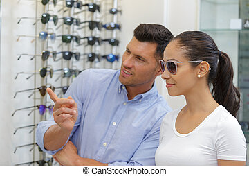 woman trying on sunglasses in opticians