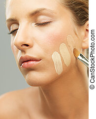 woman trying shades of foundation on jaw - closeup portrait...