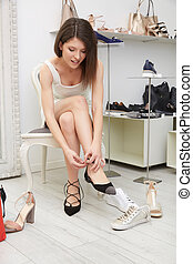 Woman trying  shoes and bags sitting in a shop