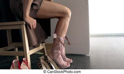 Woman trying stylish beige boots - Crop female sitting on ...
