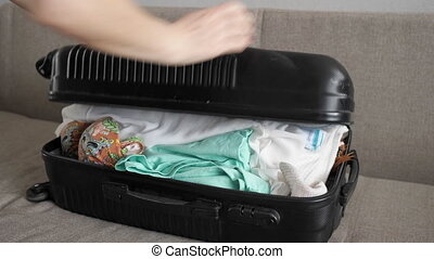 woman trying to close overflow suitcase close up