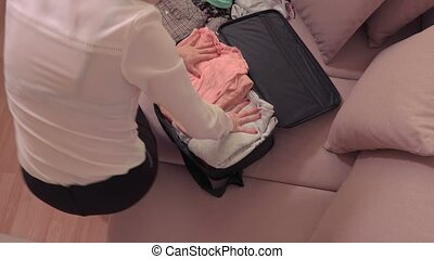 Woman trying to close suitcase on bed at home top view