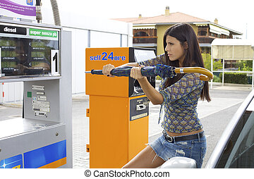 Woman trying to destroy gas station with umbrella