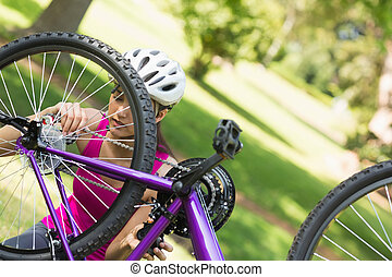 Woman trying to fix chain on mountain bike in park - Young...