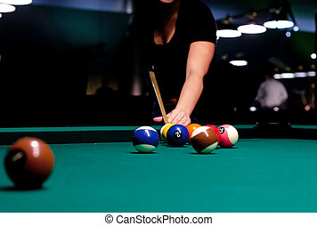 Woman trying to hit the ball in billiard